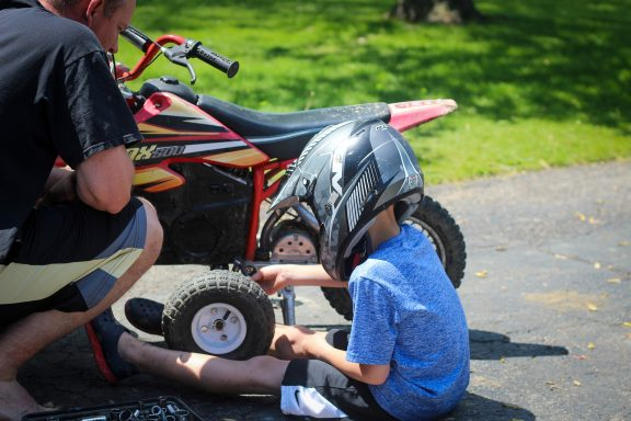 child working on dirt bike with father