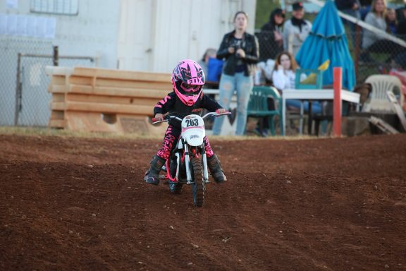 young child riding motocross dirt bike with pink protective gear